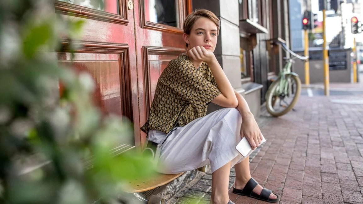 Uma jovem sentada em uma varanda do lado de fora