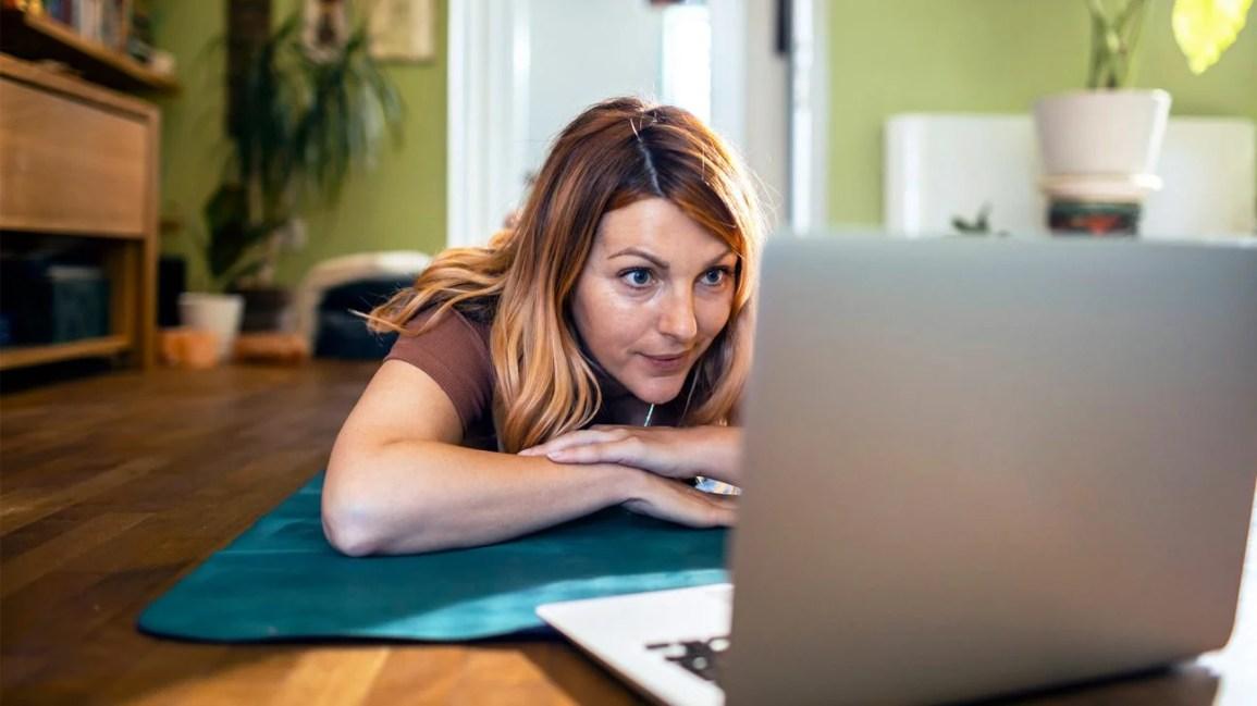 Mulher deitada na esteira de ioga olhando para o laptop