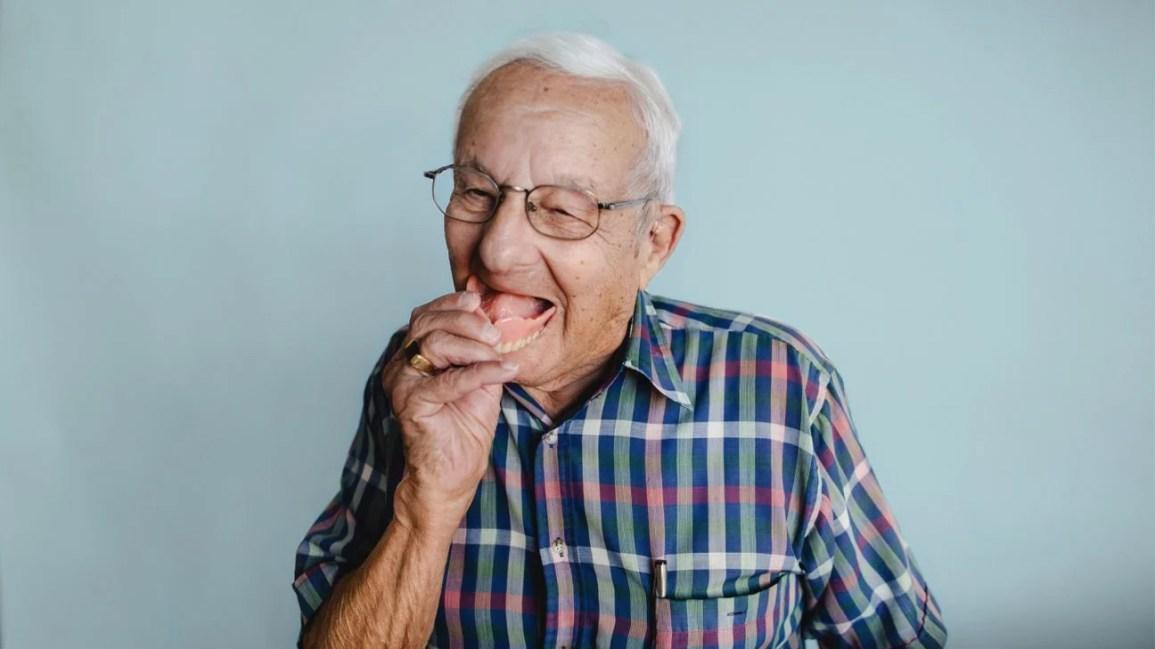 limpando dentaduras, homem tirando dentaduras da boca