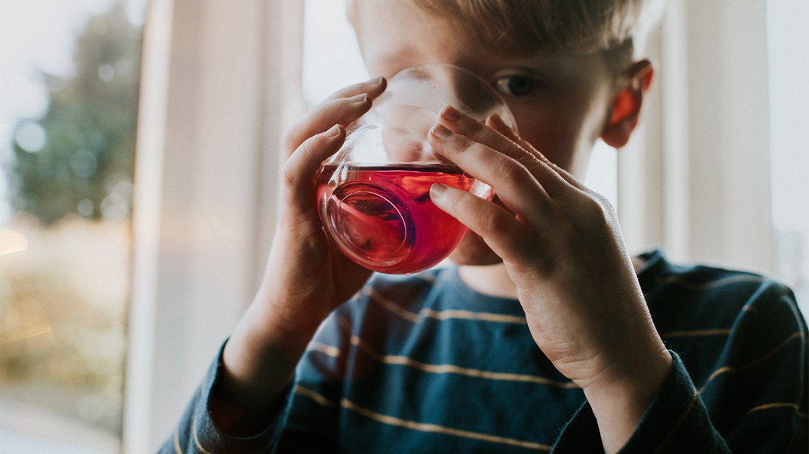 A boy drinking red juice from a glass