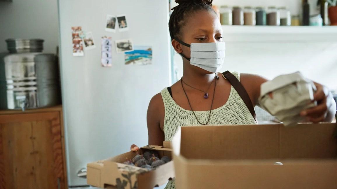 Uma mulher, usando uma máscara facial, desempacota mantimentos em sua cozinha.
