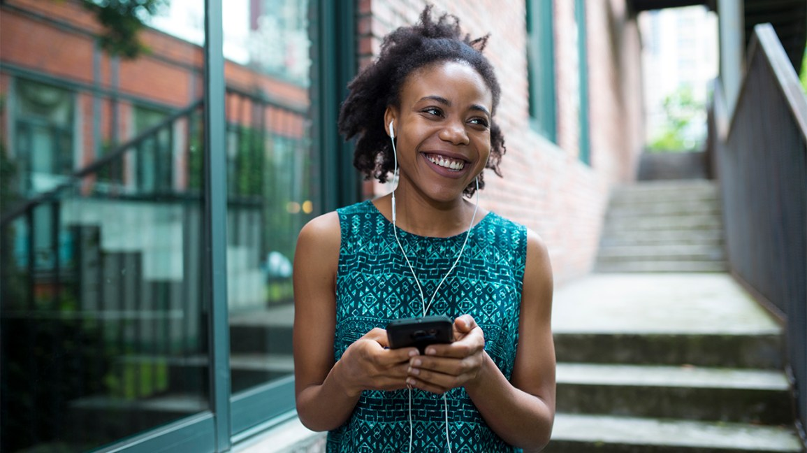 a smiling woman walking with headphones attached to her phone