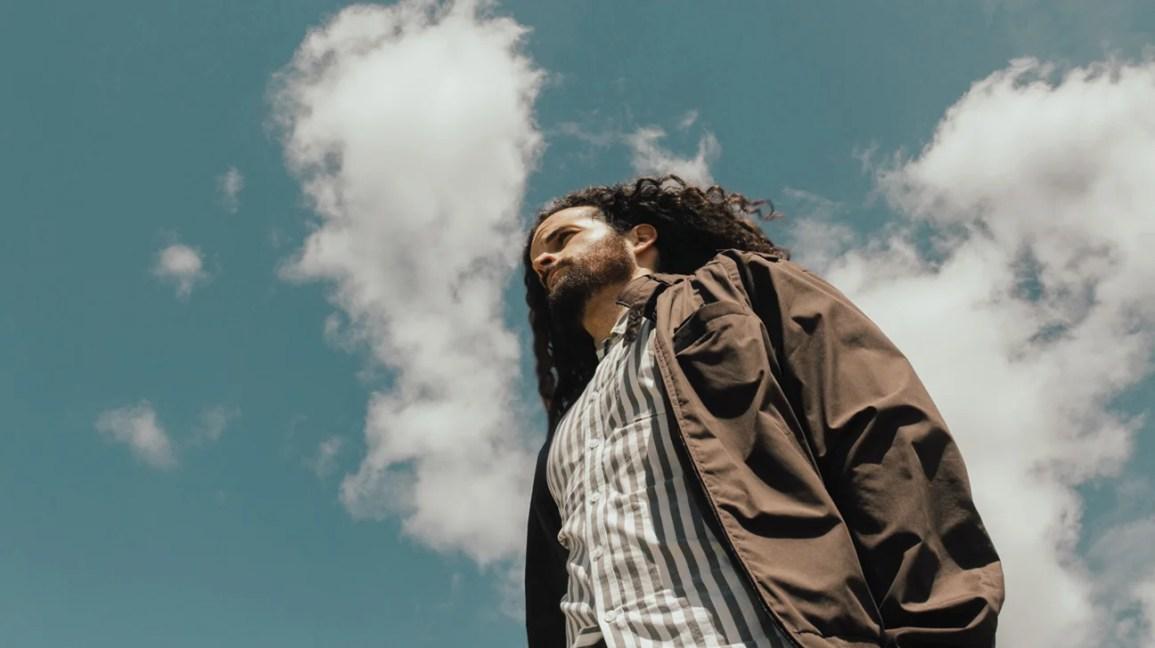 Bir adam, başının üzerinde büyük bulutlarla dışarıda duruyor.