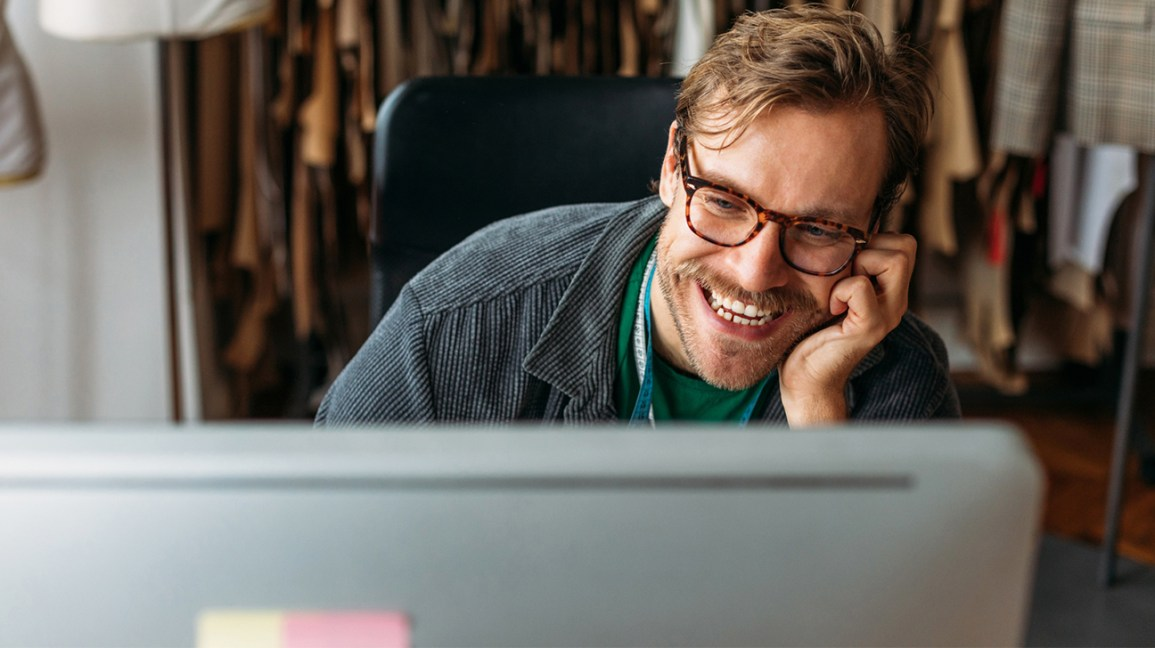 bir bilgisayara bakarken gülümseyen genç bir adam