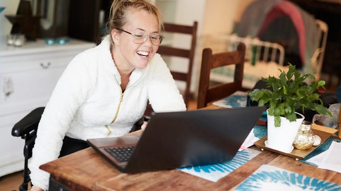 Uma mulher se senta à mesa em sua casa enquanto participa de uma sessão de psiquiatria online.