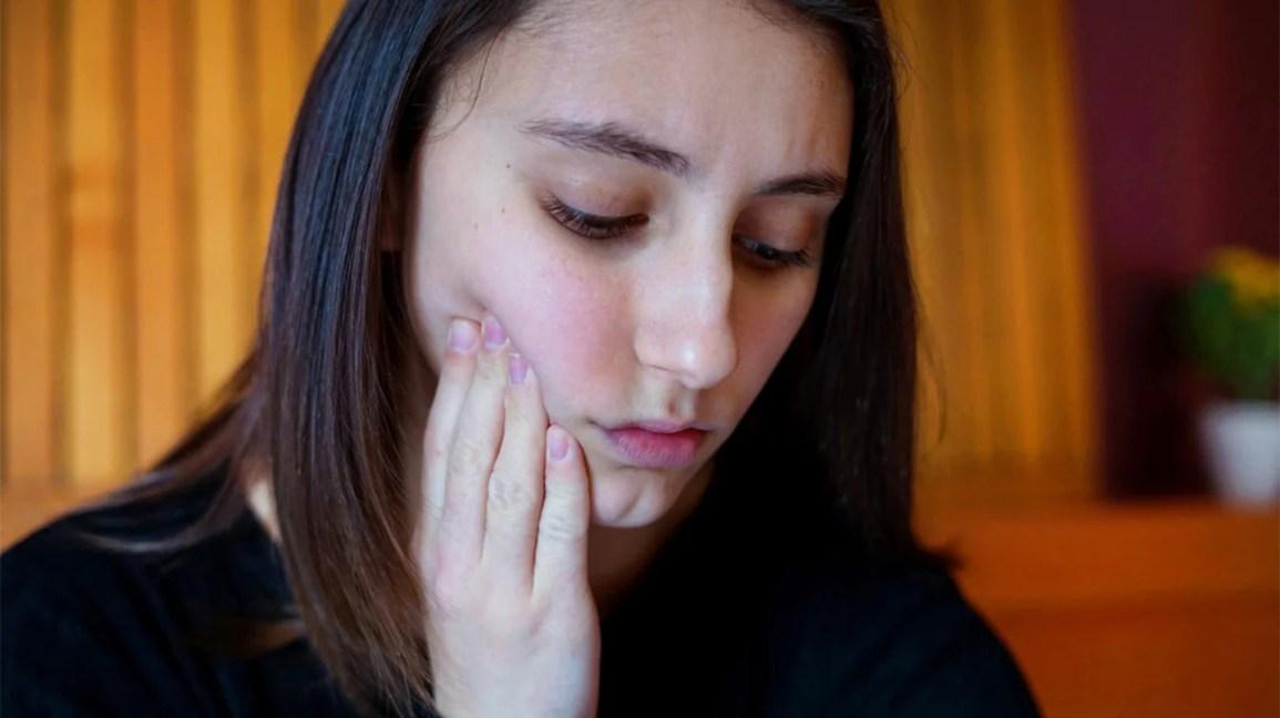 alívio de emergência para dor de dente, mulheres jovens segurando o queixo