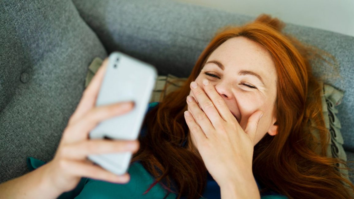 mulher cobrindo a boca e rindo enquanto conversa com o namorado