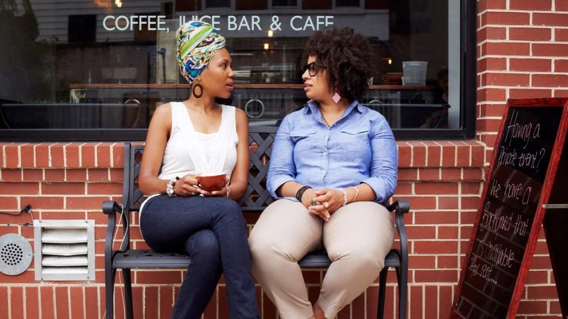 imagem de duas pessoas conversando enquanto estão sentadas em um banco do lado de fora de uma cafeteria