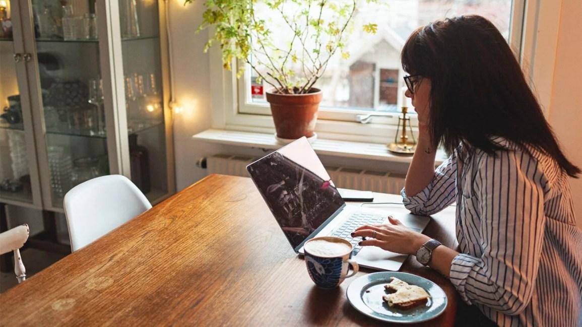 mulher perdendo no laptop enquanto toma o café da manhã na mesa