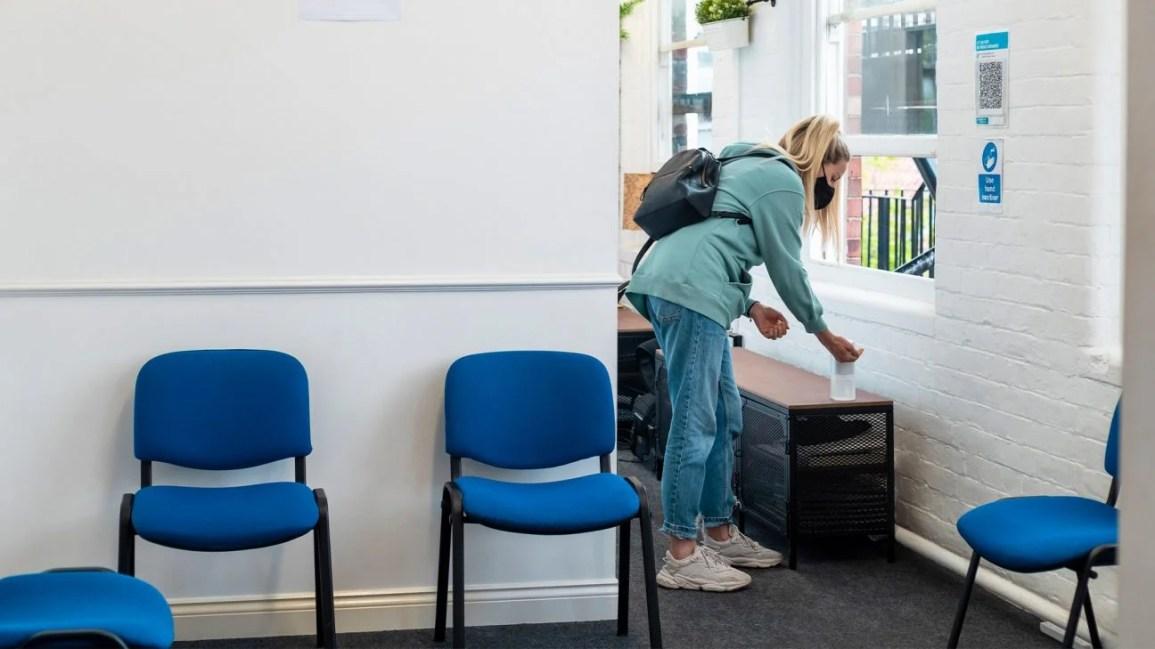 efeitos colaterais do desinfetante para as mãos, mulher recebendo uma bomba de desinfetante para as mãos em um escritório