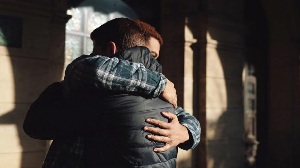 dois amigos homens se abraçando do lado de fora