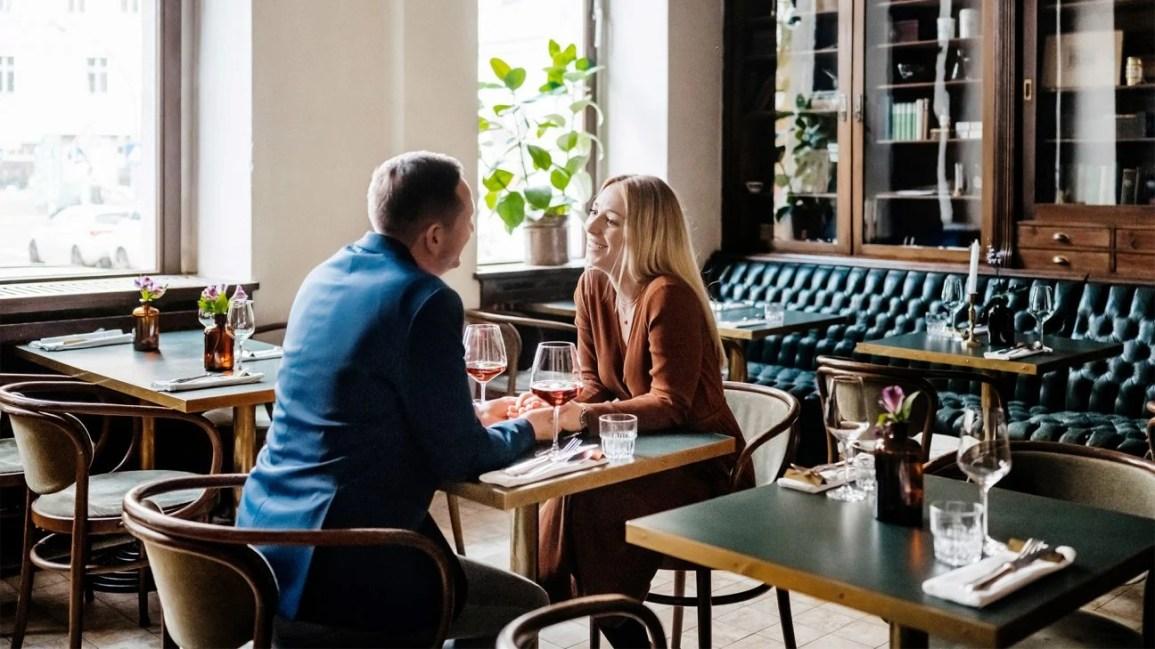 Güneşli bir restoranda oturup şarap içerken bir erkek ve bir kadın el ele tutuşur.