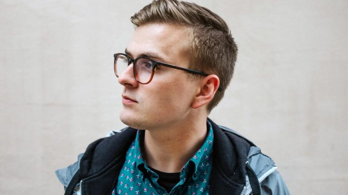 Retrato de uma pessoa com cabelo castanho claro cortado e óculos castanhos olhando para longe