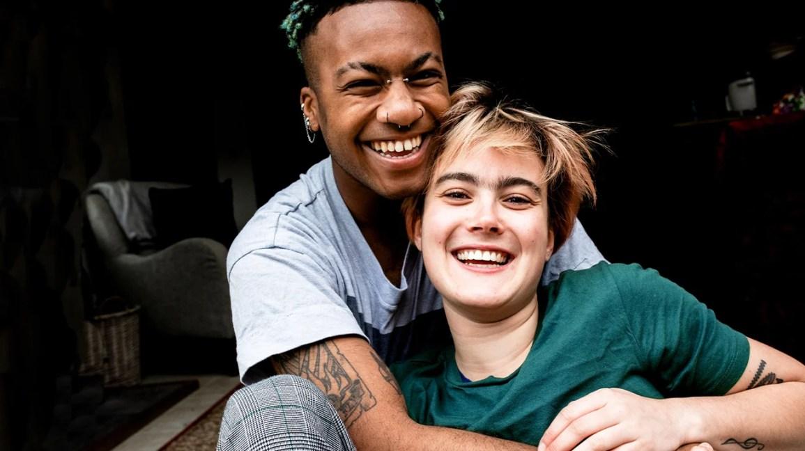 casal assexuado sentado junto sorrindo e rindo