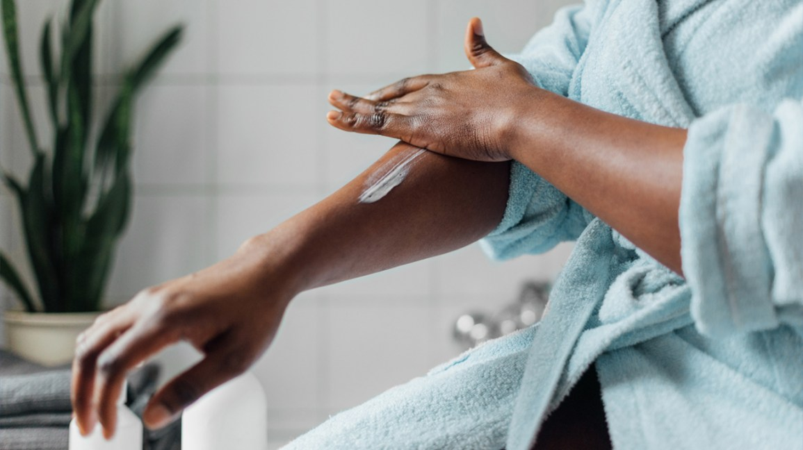 Black woman putting lotion on eczema