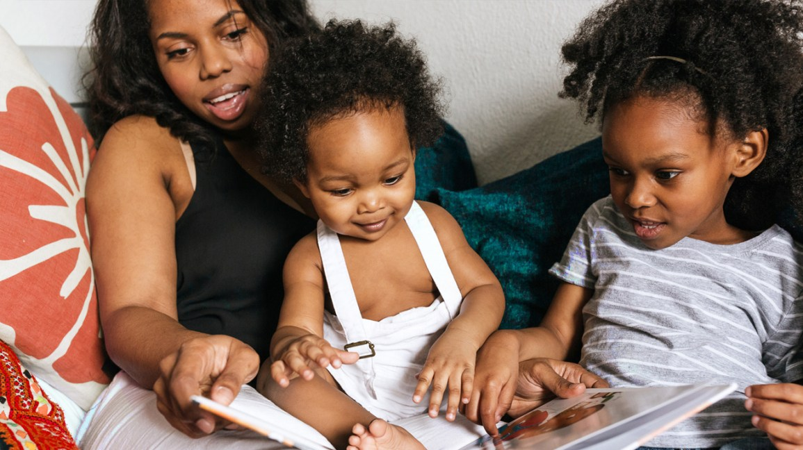 mãe lendo para a criança sentada no colo com um livro de imagens