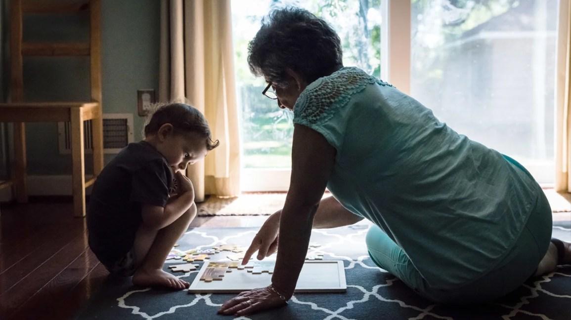 adulto e criança completam o quebra-cabeça juntos