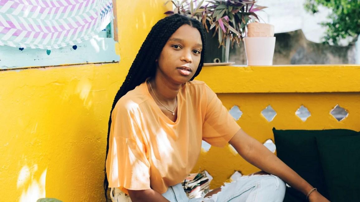 sarı duvarın önünde oturan genç kadın