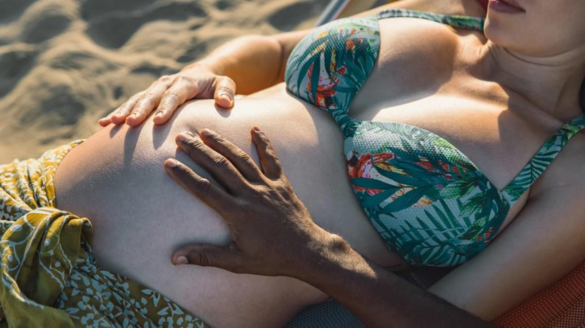 grávida deitada na praia com o parceiro