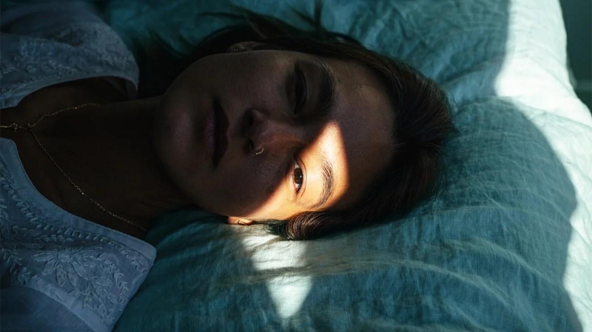 close do rosto de um homem deitado na cama com um raio de sol na testa