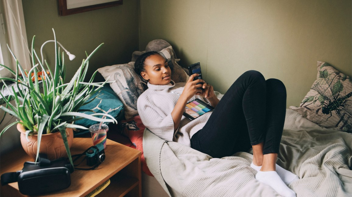 image of a teen laying on their bed with their knees up, looking down at the cell phone in their hands