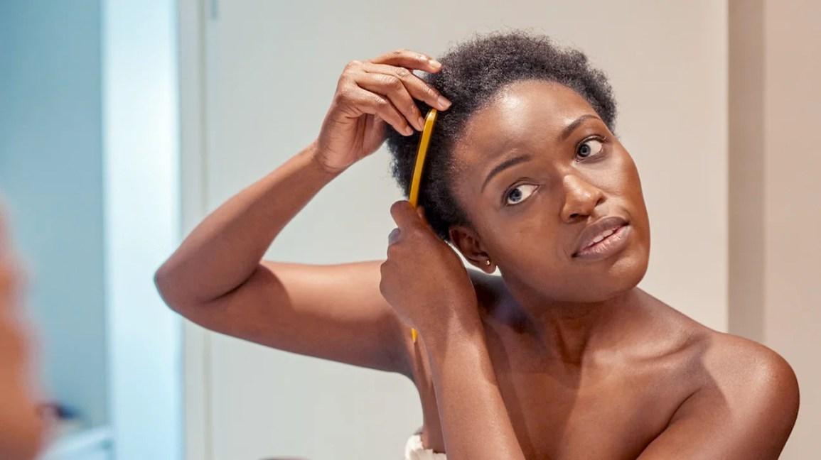mulher usando toalha penteando o cabelo no espelho