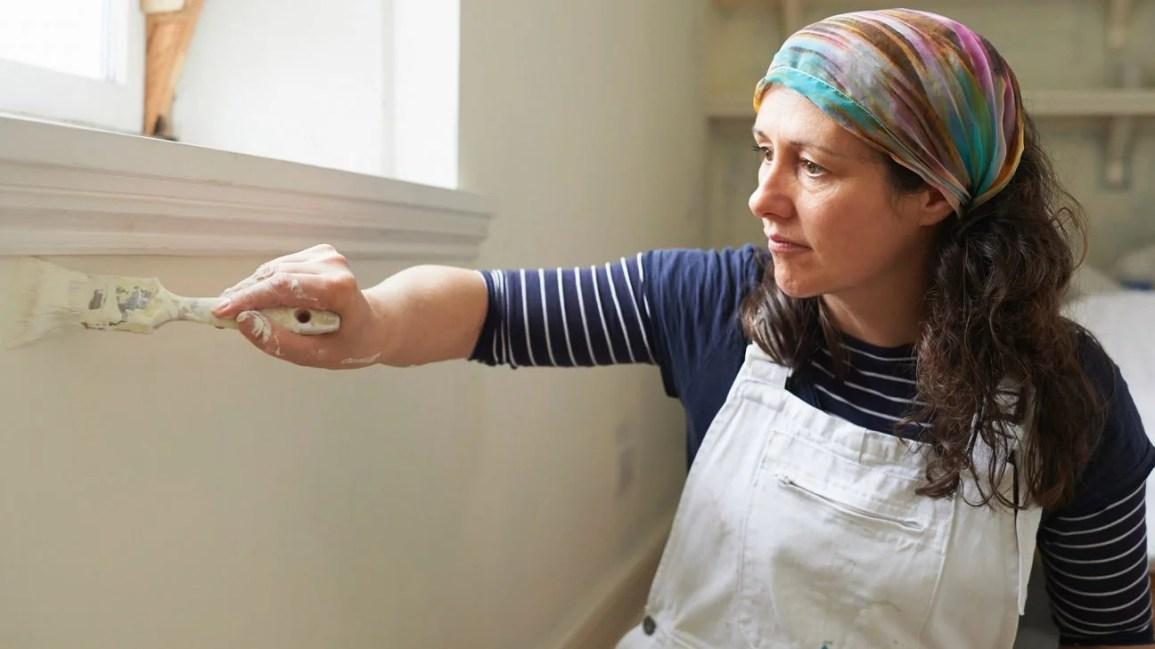 mulher ajoelhada de macacão pintando uma parede branca