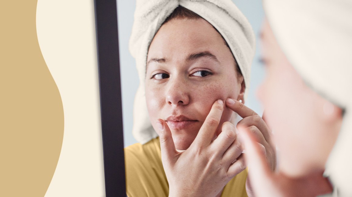 Woman checking her skin on a mirror