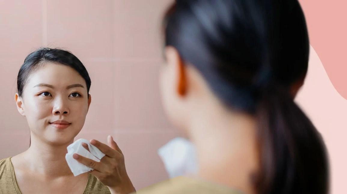 Mulher se olhando no espelho, segurando um lenço de papel