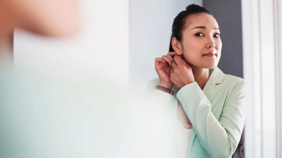 mulher de camisa azul colocando brincos no espelho