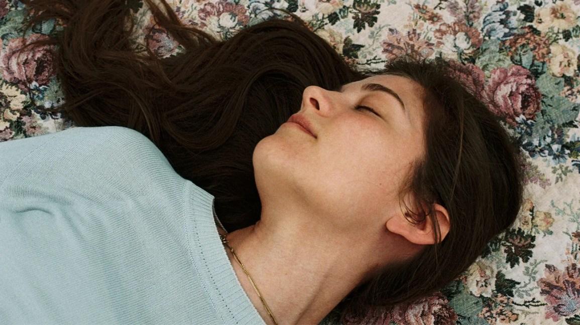 mulher com longos cabelos escuros deitada com os olhos fechados