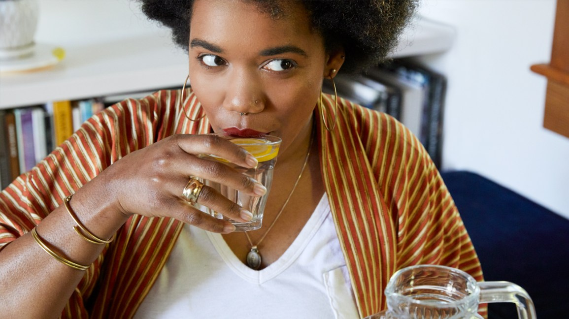 pessoa tomando um copo de água com limão