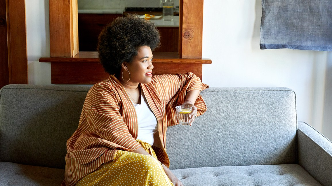 Woman sitting on the couch drinking a glass of water