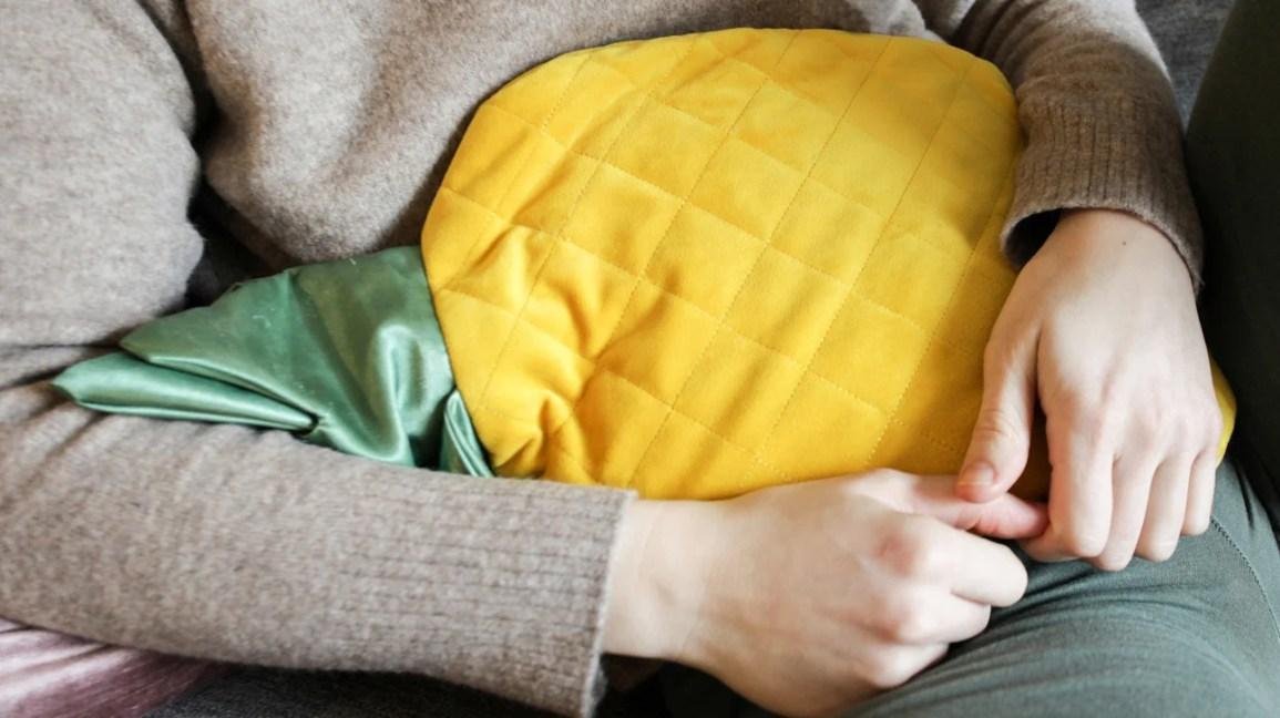 imagem recortada de uma pessoa aplicando uma almofada térmica amarela no abdômen