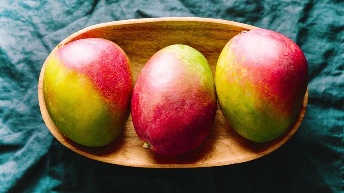 whole mangos in a wooden bowl