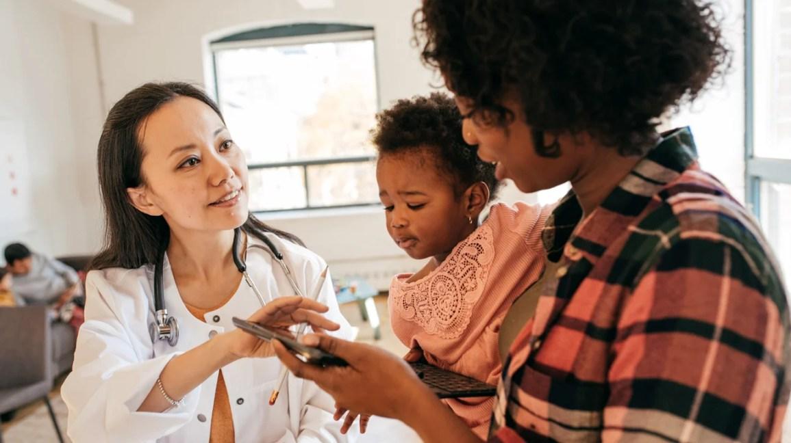 médico fala com pai segurando criança