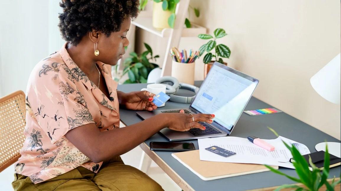 mulher insere informações de cartão de crédito no computador