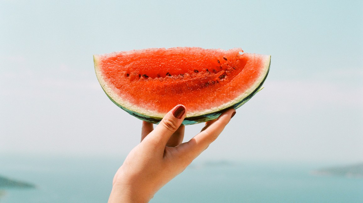 holding up a slice of watermelon