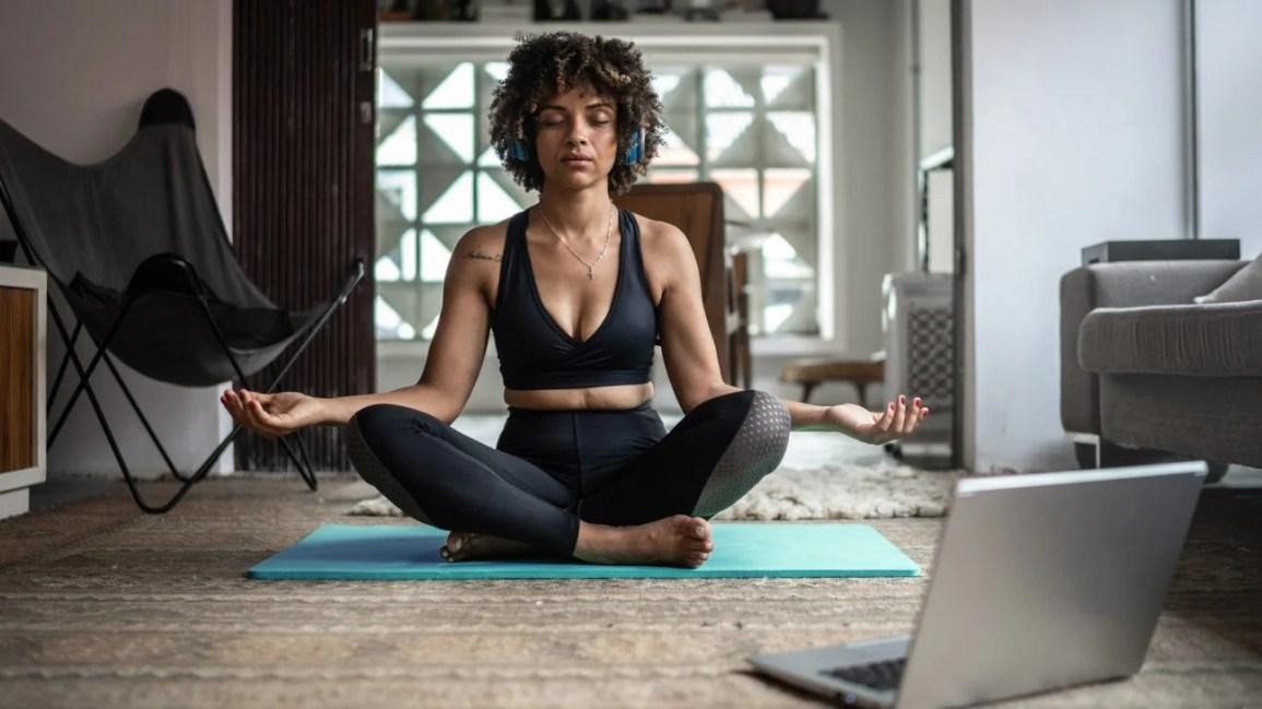 mulher sentada no chão praticando meditação em frente ao laptop
