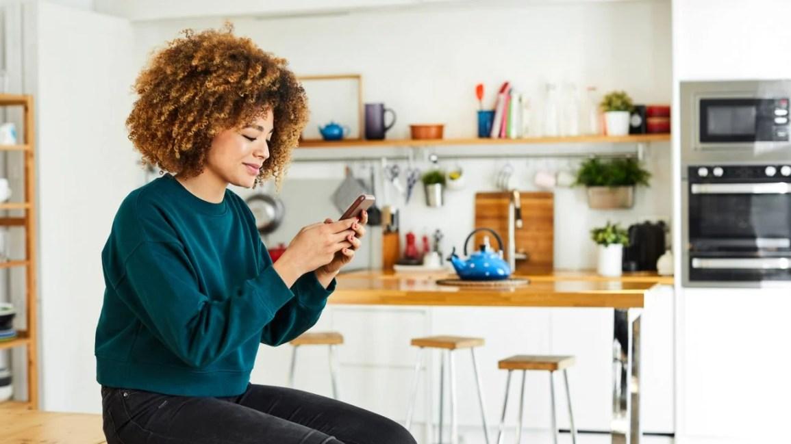 Mulher usando smartphone em casa para teleterapia