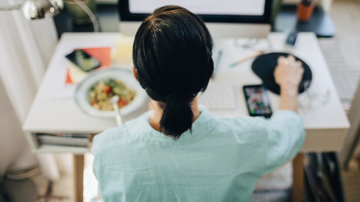 Woman having lunch at her desk in front of the computer