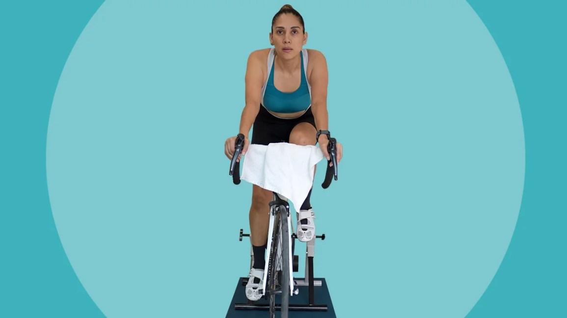 Mulher se exercitando no instrutor de bicicleta indoor