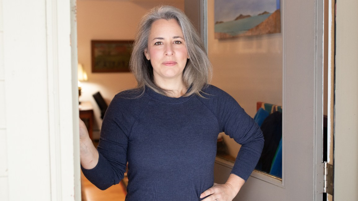 A instrutora de fitness Andrea Wool, da Autoimmune Strong, está parada na porta sorrindo