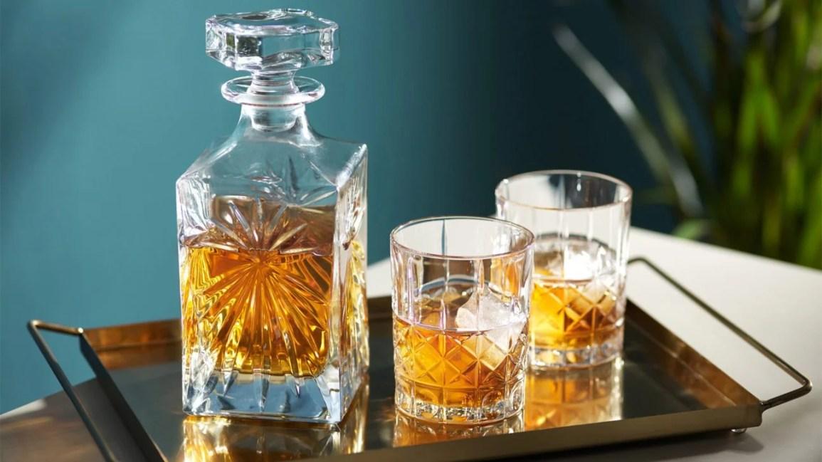 garrafa de vidro e duas classes cheias de uísque na mesa