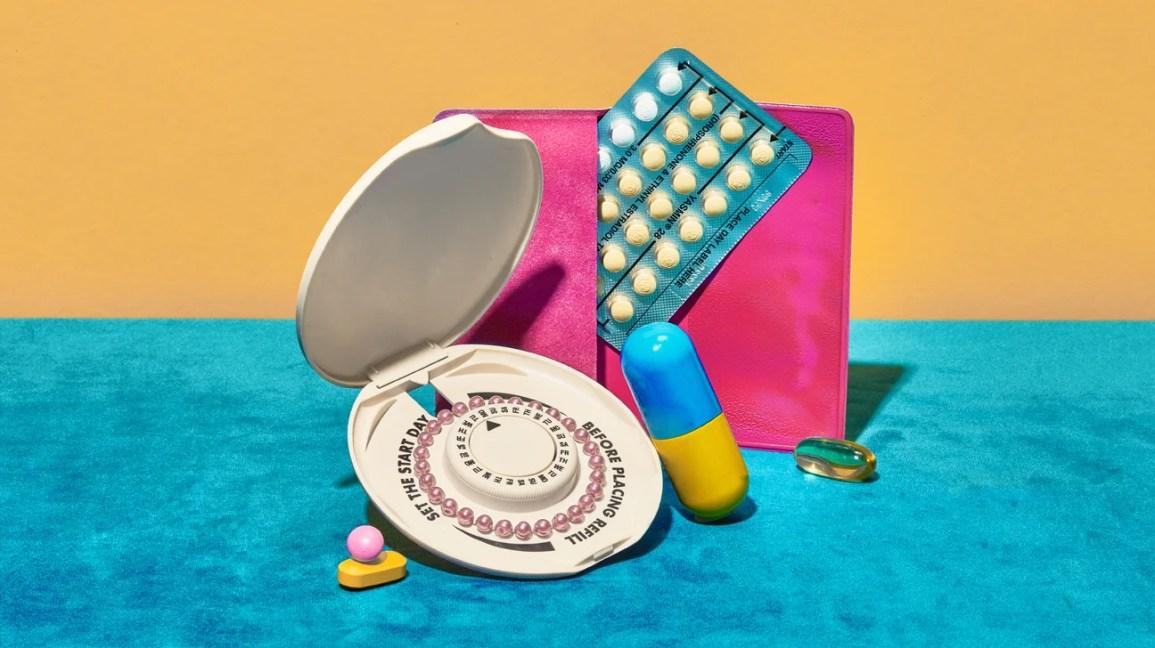 Vários tipos de pílulas anticoncepcionais são exibidos em um tapete azul com um fundo laranja.