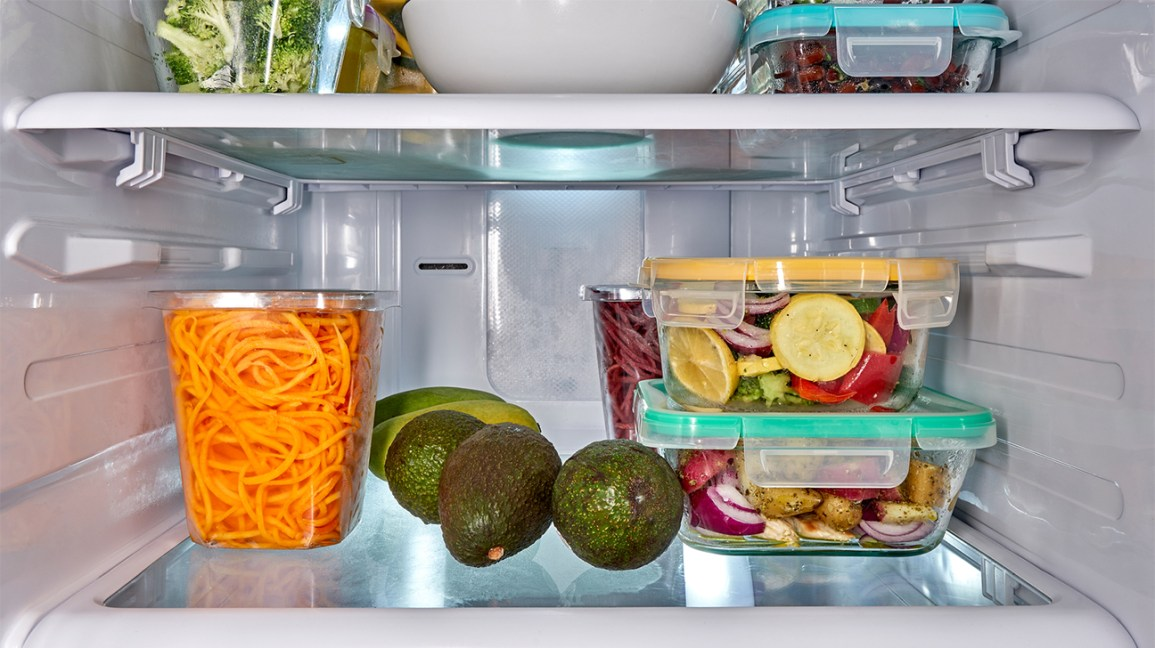 avocados and sliced vegetables in containers in the fridge