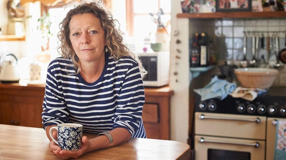 Retrato de uma pessoa encostada no balcão da cozinha, segurando uma xícara de café