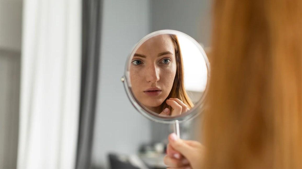 femme examinant le visage dans le miroir