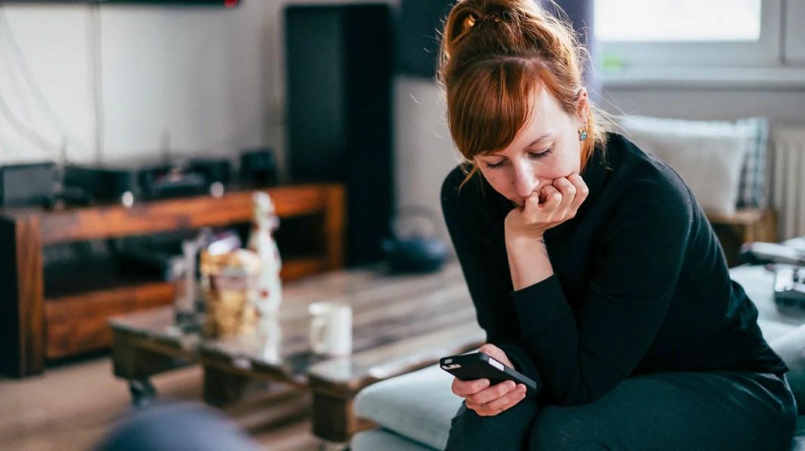 mulher sentada com o cotovelo na coxa olhando para o smartphone