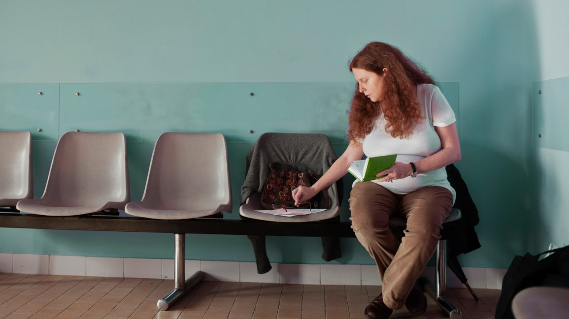 person with long curly auburn hair sitting in a waiting room
